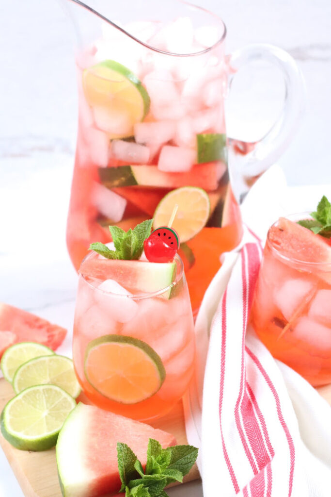 clear glass pouring pitcher with watermelon sangria, slices of watermelon and lime slices