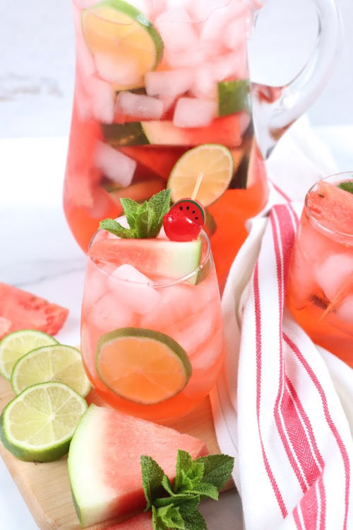stemless glass of sangria with slices of watermelon, lime slices, pouring pitcher behind
