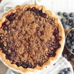 Blueberry crumble pie in white pie dish on white marble, fresh blueberries around.