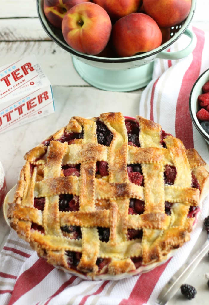 Homemade berry pie with lattice weaved crust. Mint green enamelware colander in background with fresh peaches.