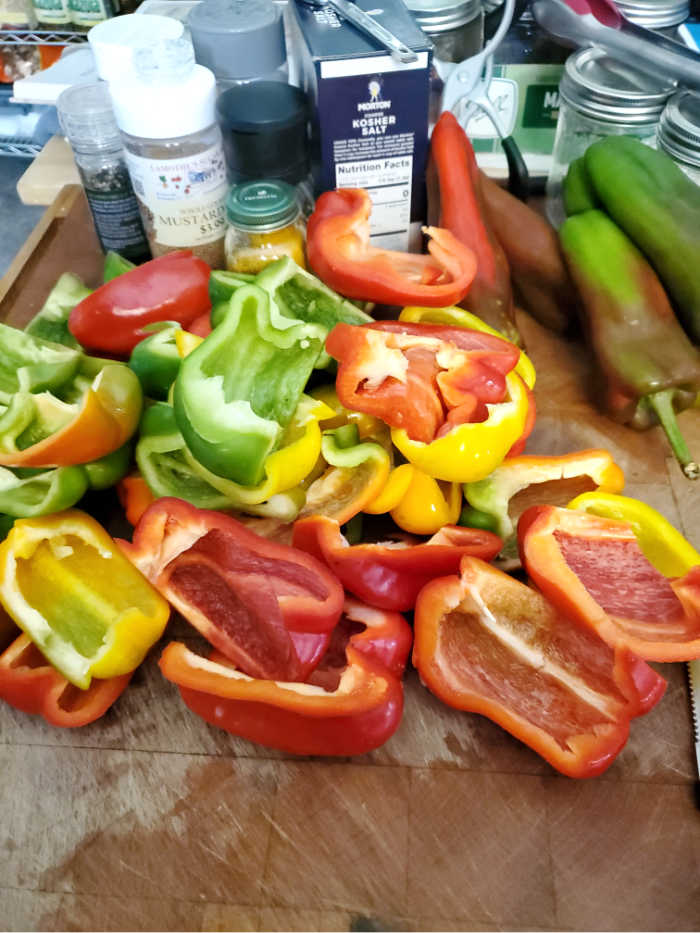 halves of bell peppers being sliced on butcher block for pickled peppers