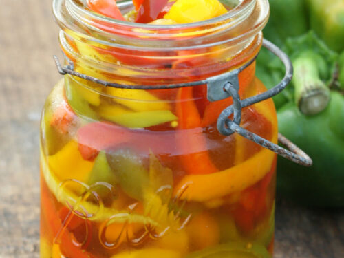Multi colored peppers in vintage Mason jar on wood board.