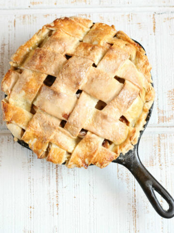 Pie with lattice crust in a small cast iron skillet on white reclaimed wood.