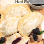 blackberry hand pies leaning up against each other on wooden cutting board