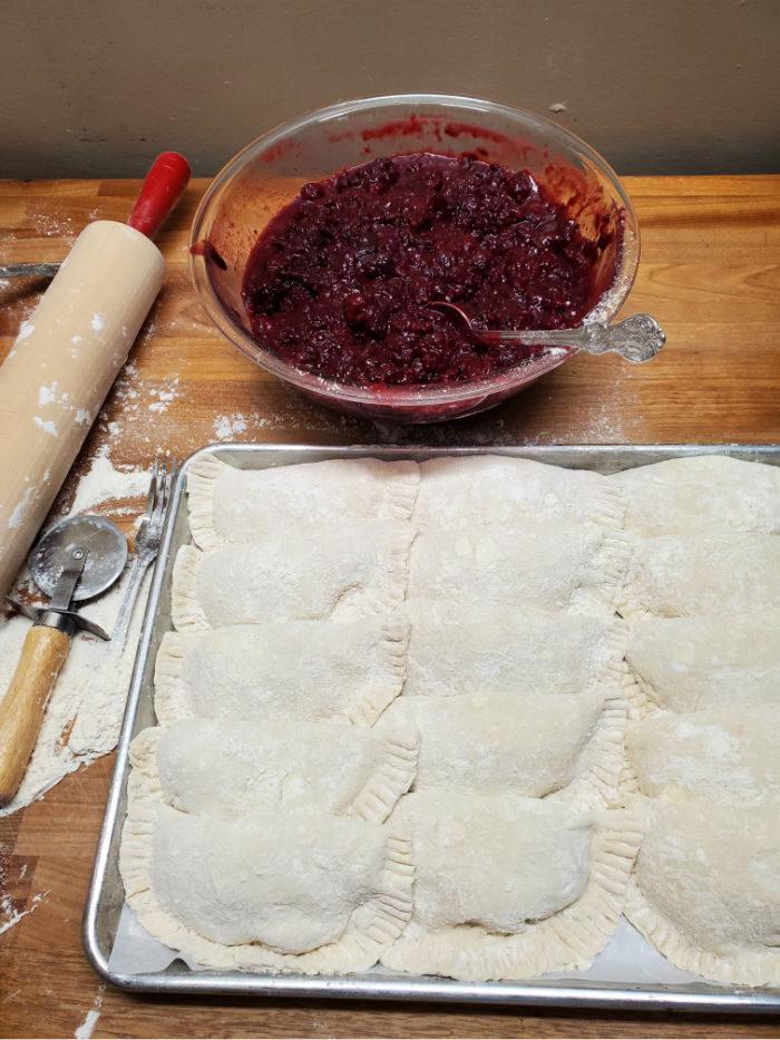 uncooked hand pies on a half sheet pan, overlapping each other. Blackberry pie filling in a clear glass bowl behind the tray. Red handled rolling pin to the left