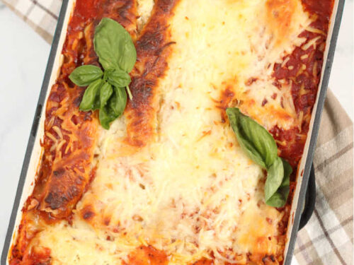 rectangle teal color baking dish with homemade lasagna, fresh basil leaves on top