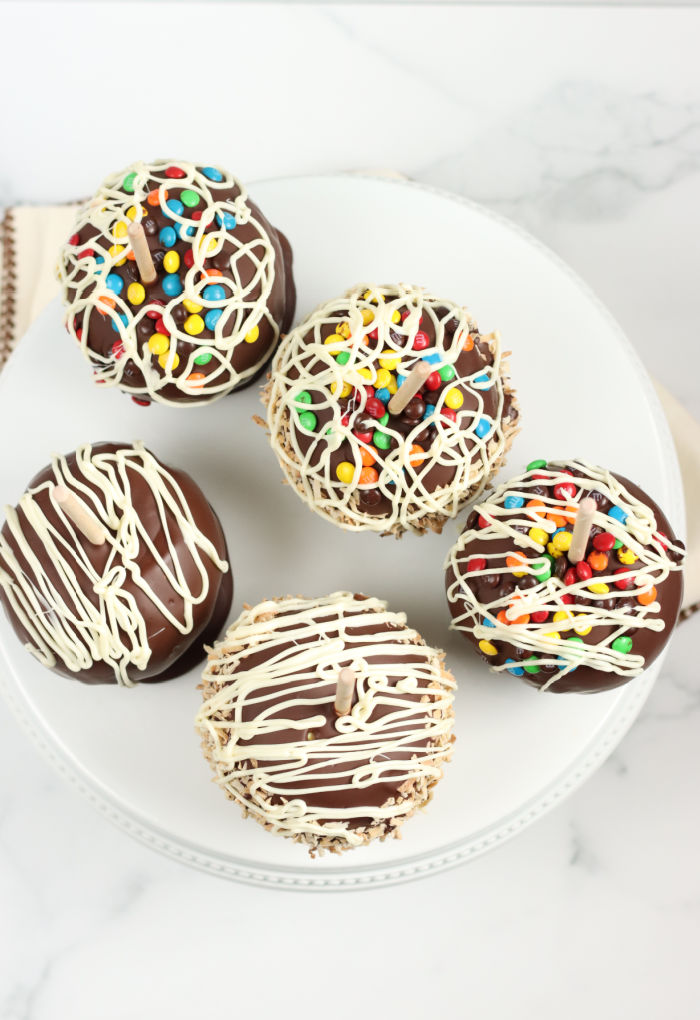 Caramel apples dipped in chocolate and drizzled with white chocolate, mini M&M candies, on a white footed cake dish.