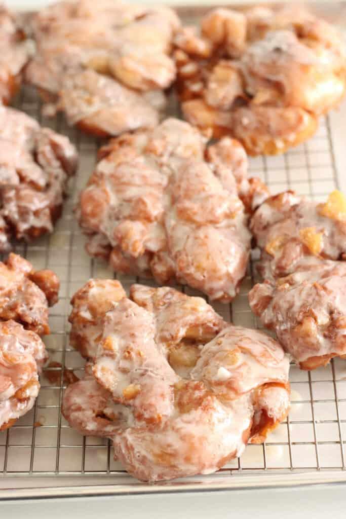 glazed apple fritters drying on baking rack
