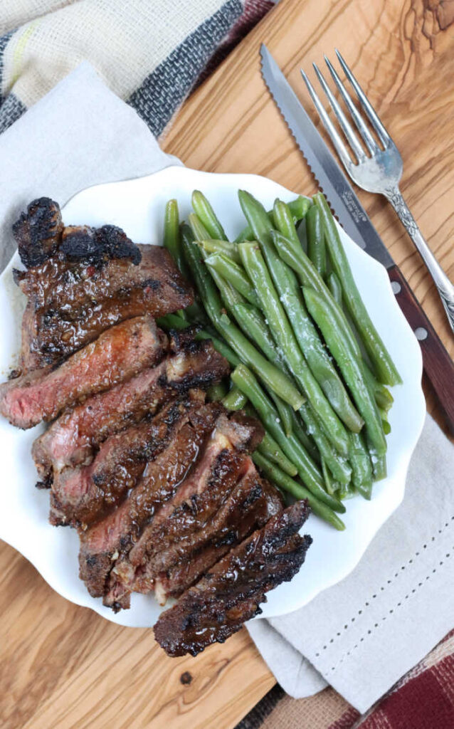 slices of grilled steak on a small white plate along side fresh green beans sprinkled with salt