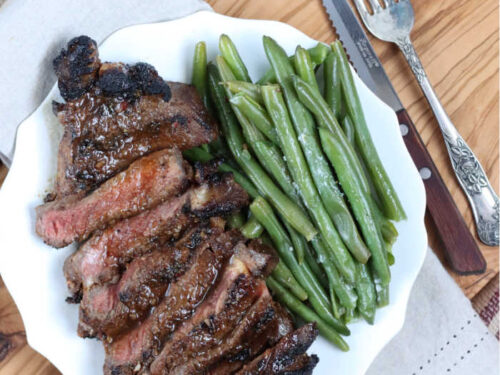 sliced grilled ribeye steak on small white plate, fresh green beans to side