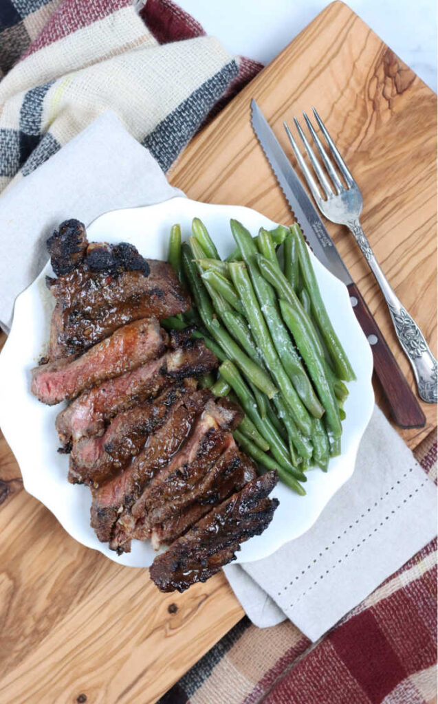 Sliced Ribeye steak on small white plate with fresh green beans. Plate sitting on a Olive wood cutting board, fork and knife to the right