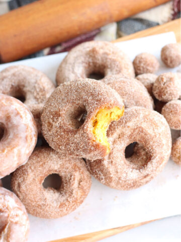 pumpkin donuts stacked on each other on wooden cutting board lined with white parchment paper, bite out of one donut