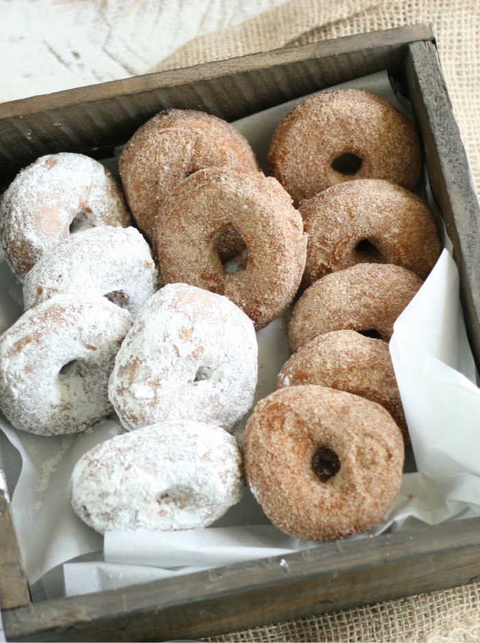 cake donuts dusted in powdered sugar, some with cinnamon sugar, leaned up against each other in a reclaimed wooden box on burlap
