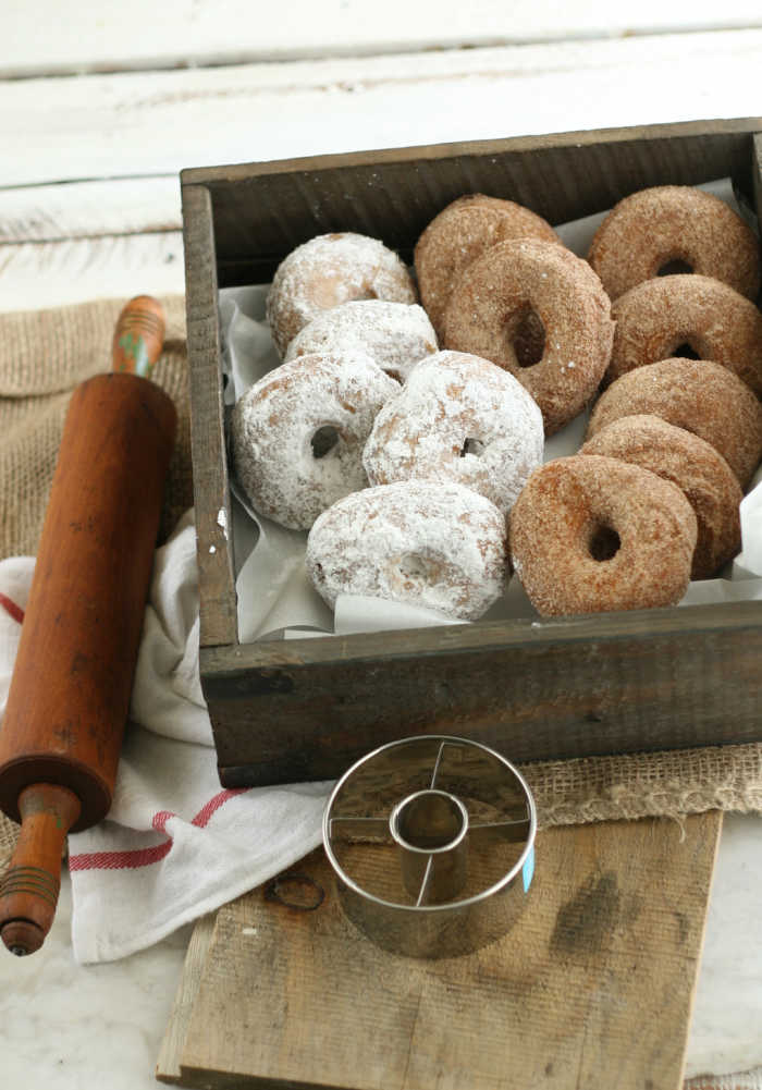 cake donuts dusted with powdered sugar, some with cinnamon sugar mixture in a reclaimed wooden box, vintage rolling pin to the left
