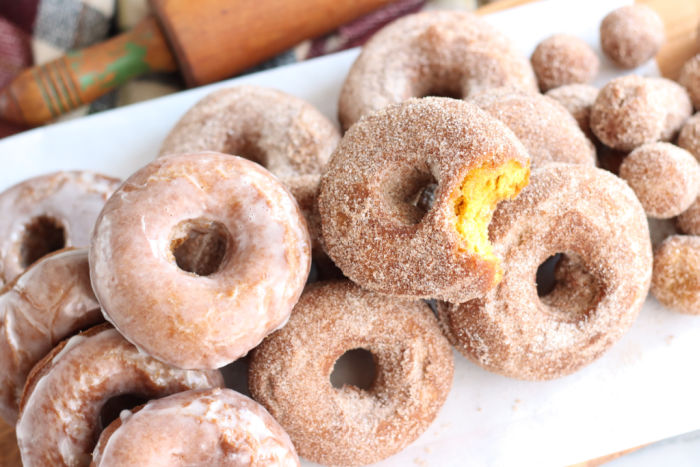 pumpkin doughnuts stacked on top of each other on a wooden cutting board. Wooden rolling pin in background