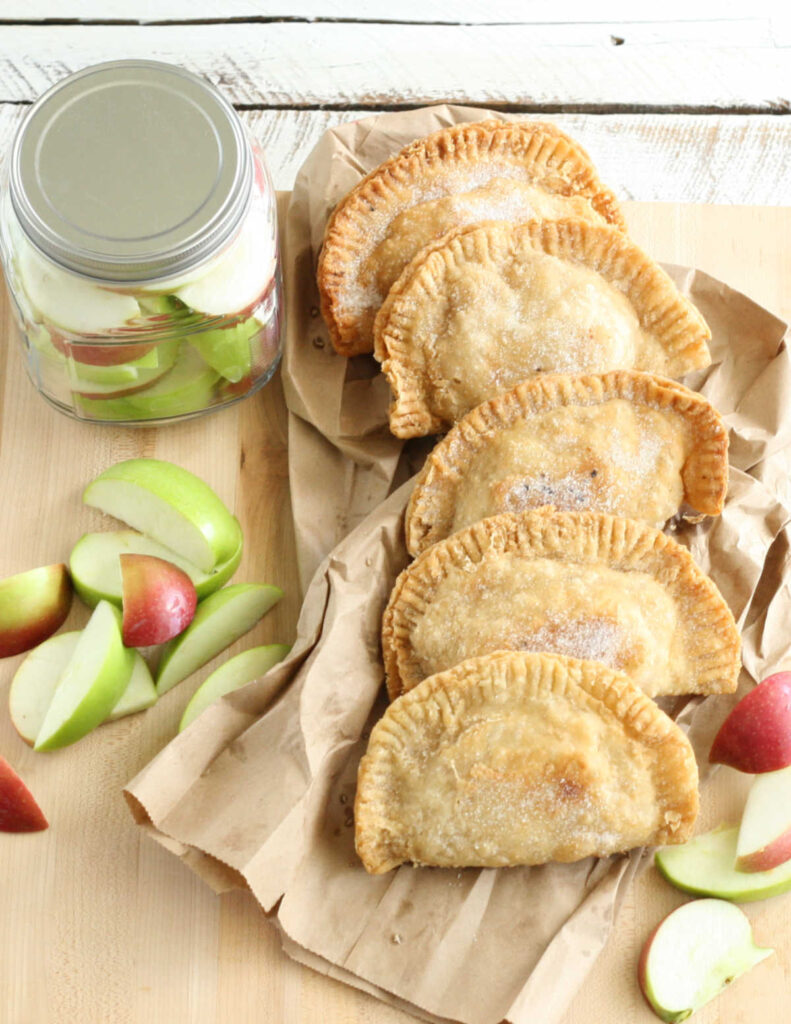 apple hand pies stacked against each other on a wooden cutting board with slices of apples.