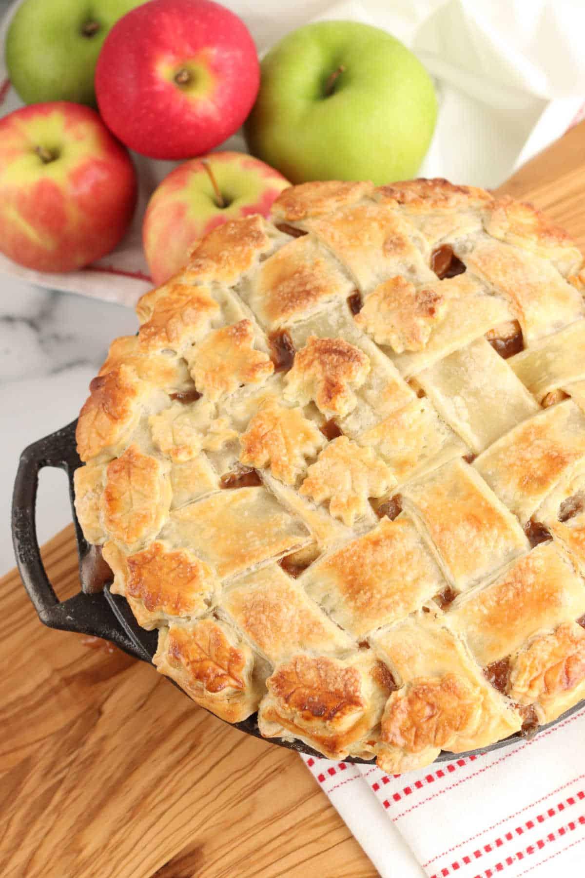 Close up of lattice pie crust on apple pie, apples in background.