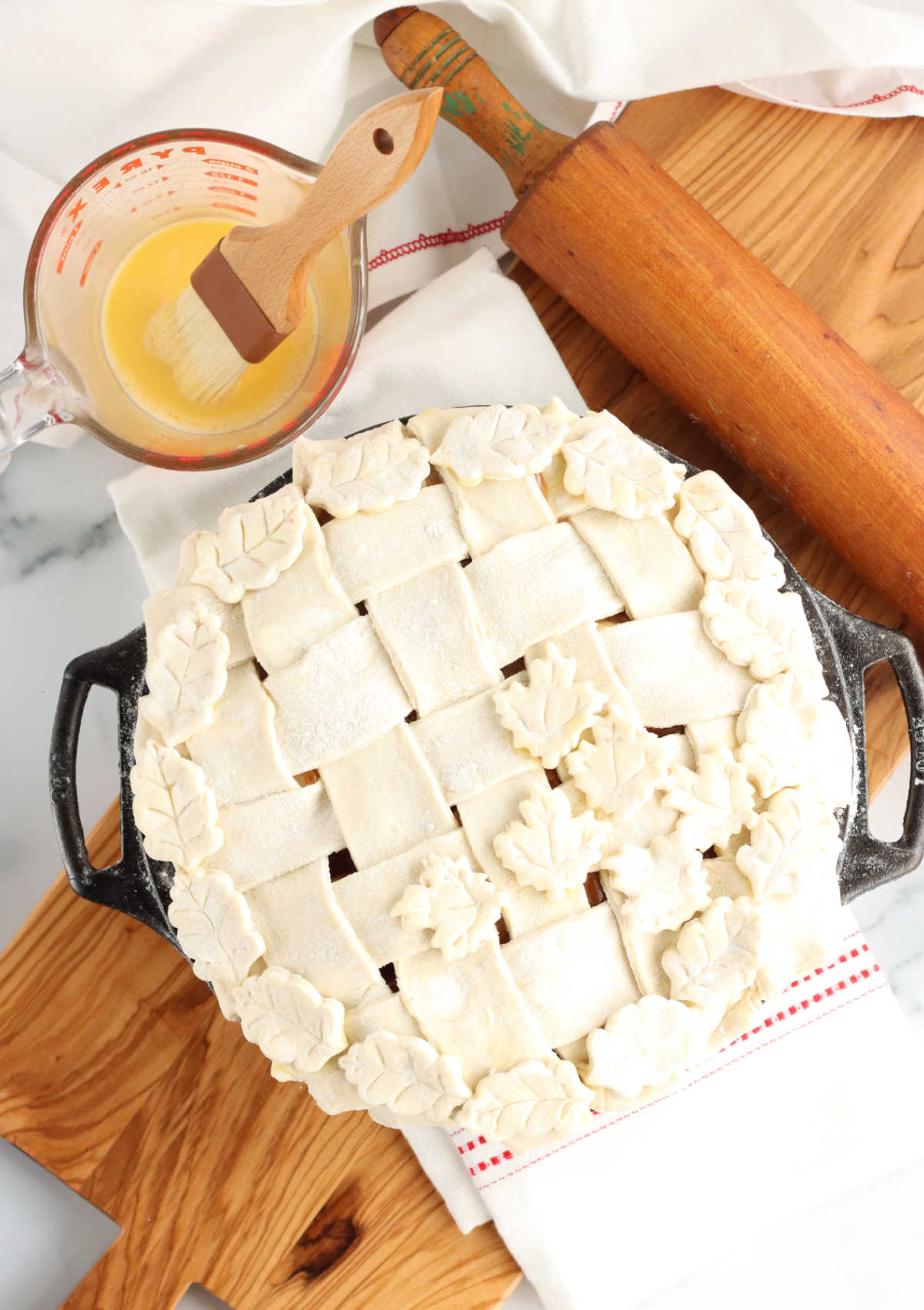 unbaked pie with lattice crust in cast iron pie pan on wooden cutting board.