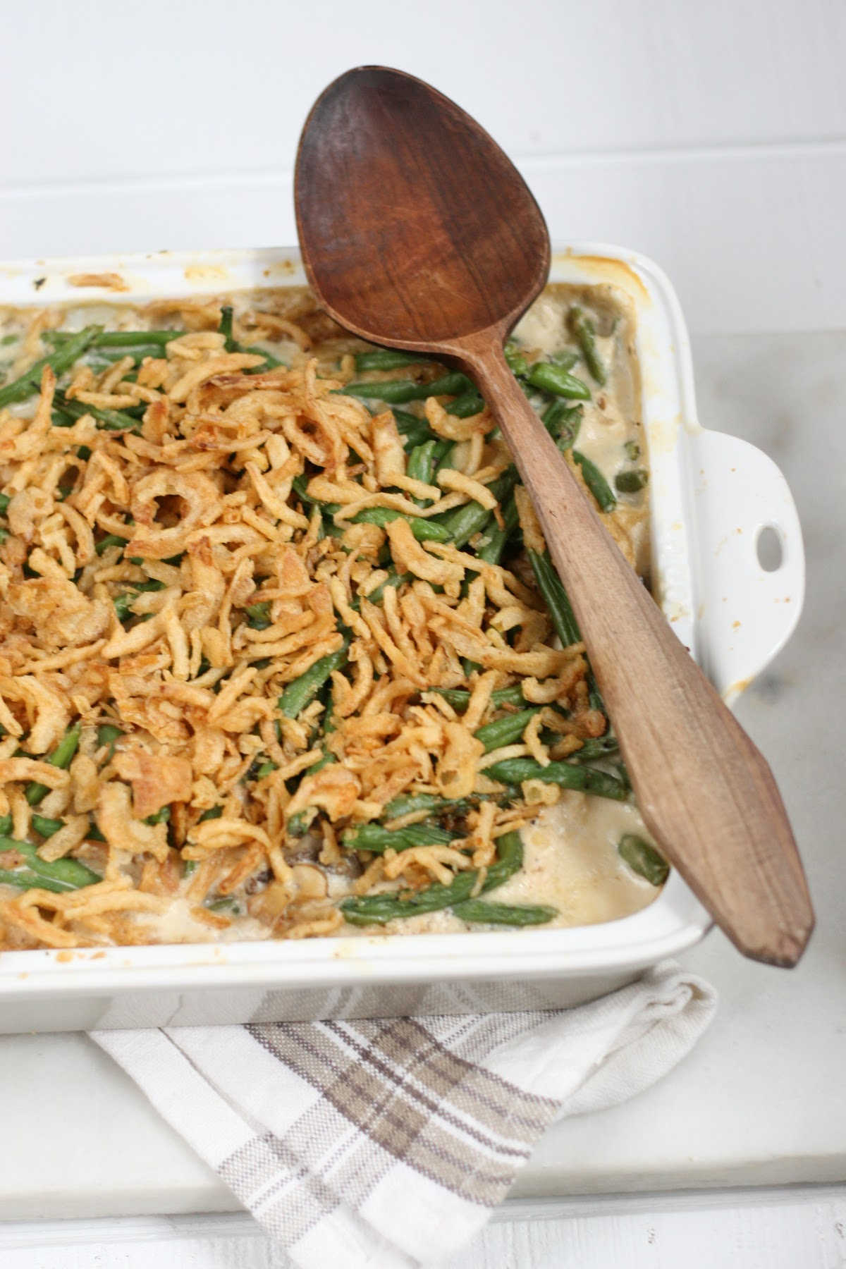 close up of white baking dish with green bean casserole, wooden spoon on right side of dish.