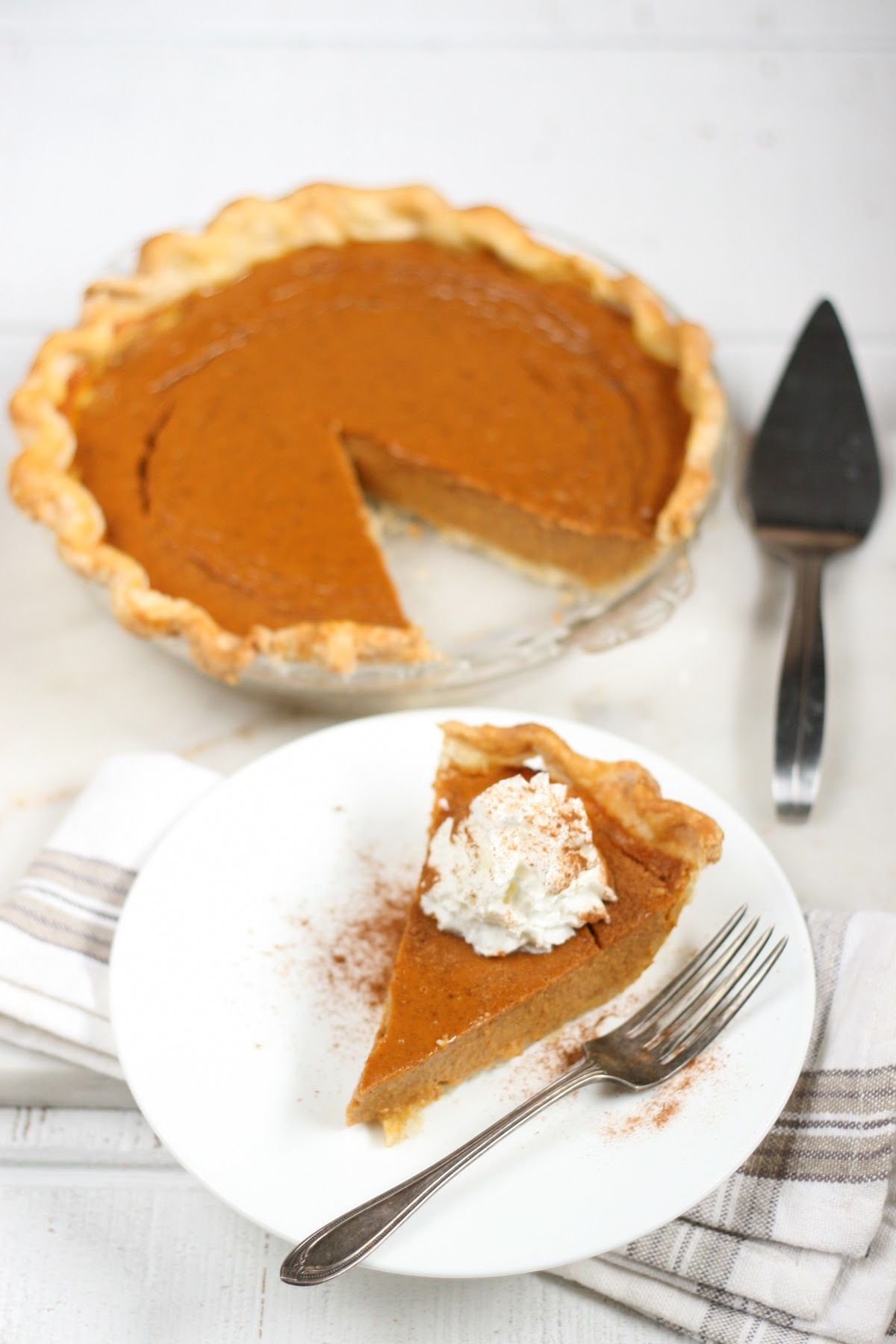 sliced pumpkin pie on white plate, full pie to the background.