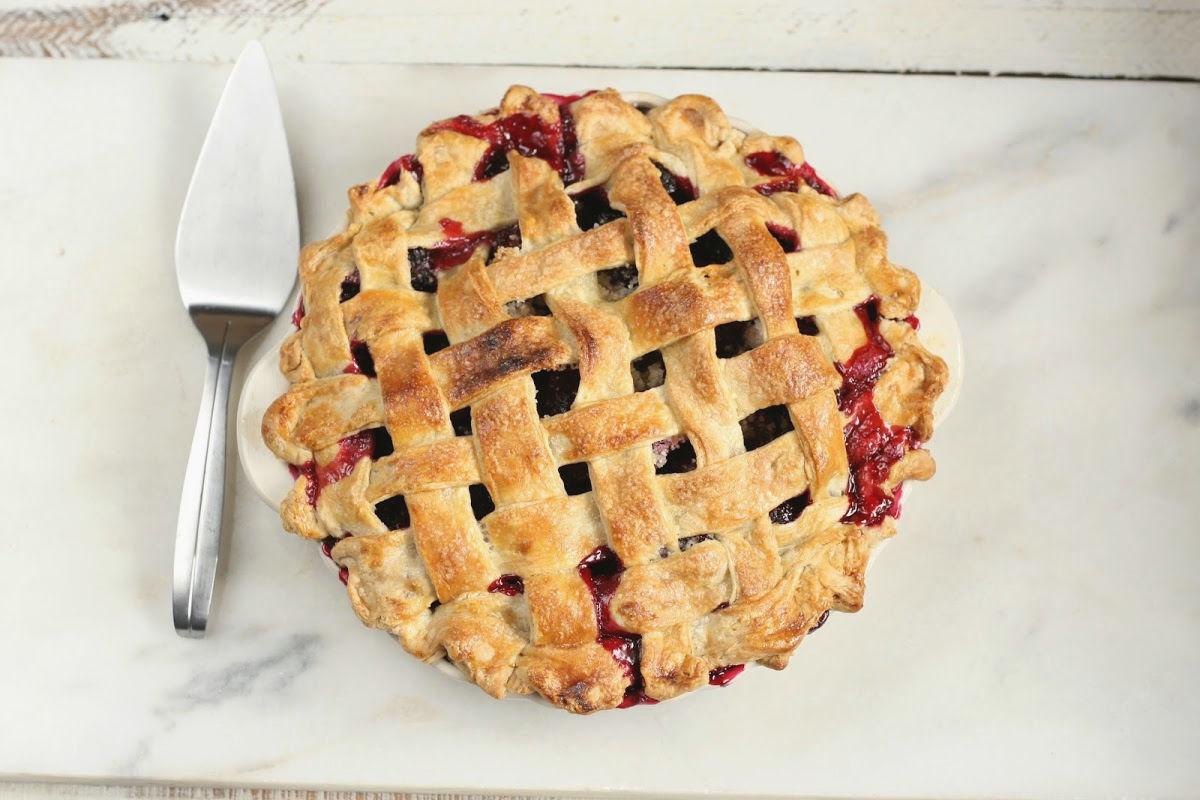 lattice pie crust on blackberry pie on white marble, metal pie server to the left.