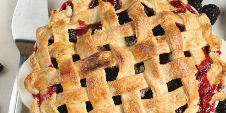 blackberry pie with lattice crust and loose berries around it on white marble.