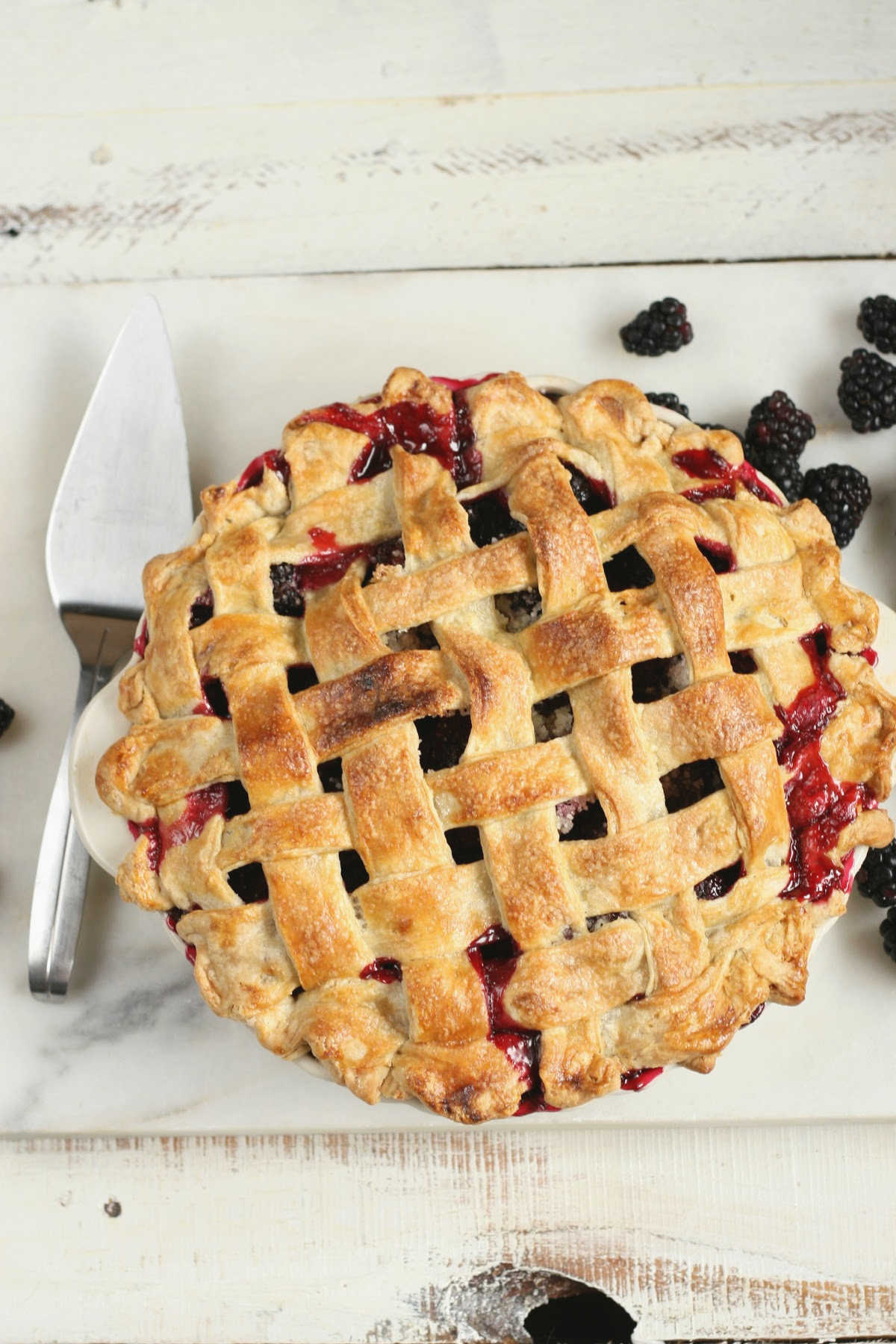 blackberry pie with lattice crust on white marble, metal server to the left.