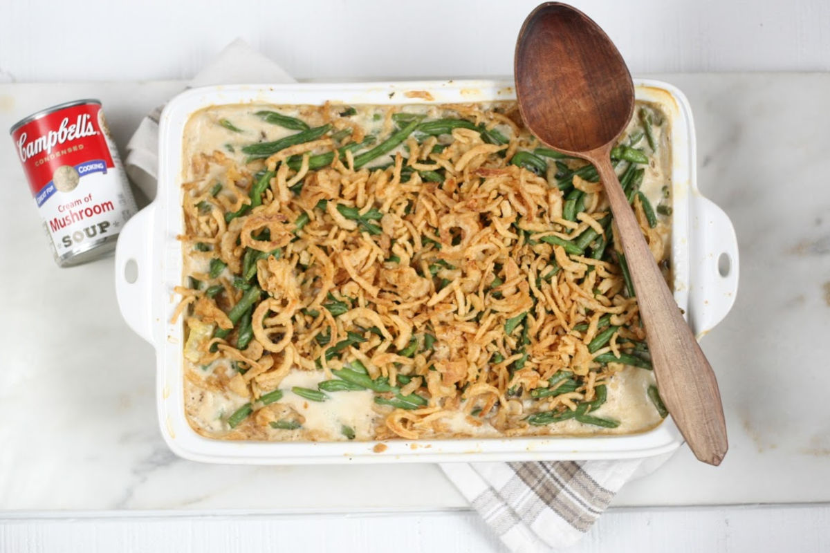 white rectangle baking dish with green bean casserole, wooden spoon on right side of dish.