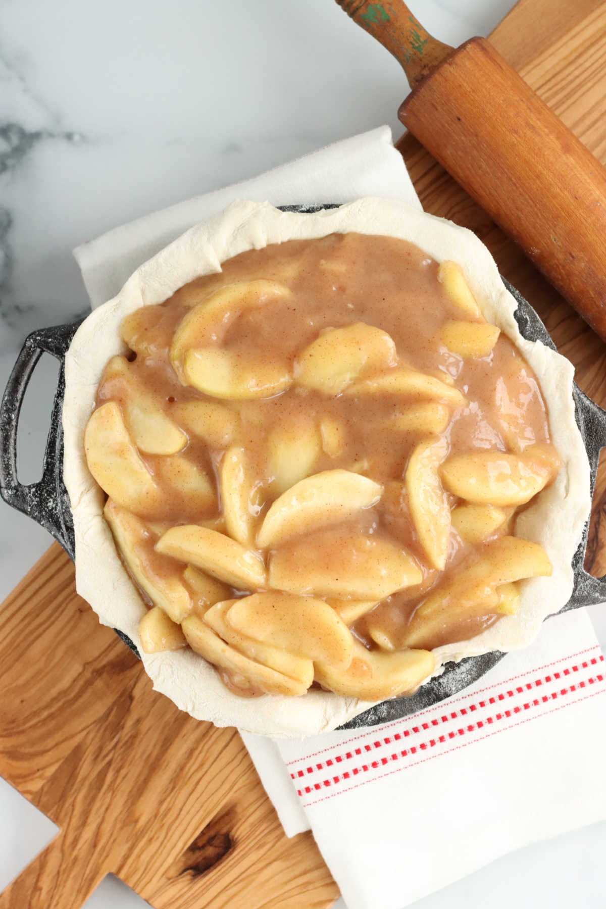 unbaked pie shell with apple pie filling on wooden cutting board, wooden rolling pin side.