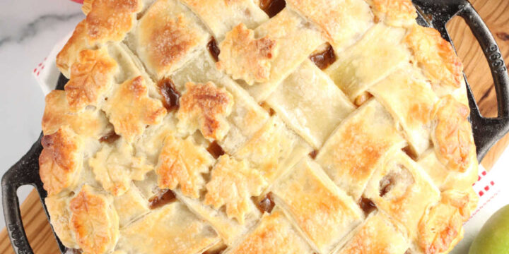 Apple pie with lattice crust in cast iron pie plate, sitting on wooden cutting board.