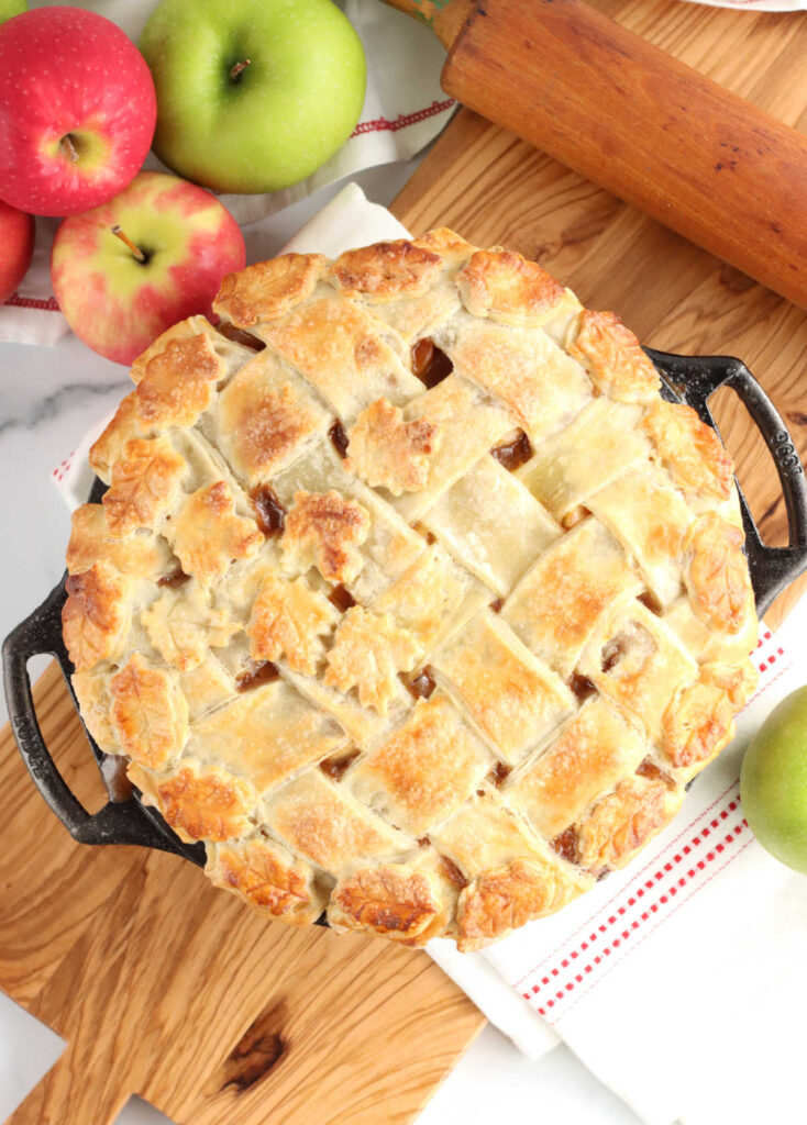 baked apple pie with lattice crust, apples around it on wooden cutting board.