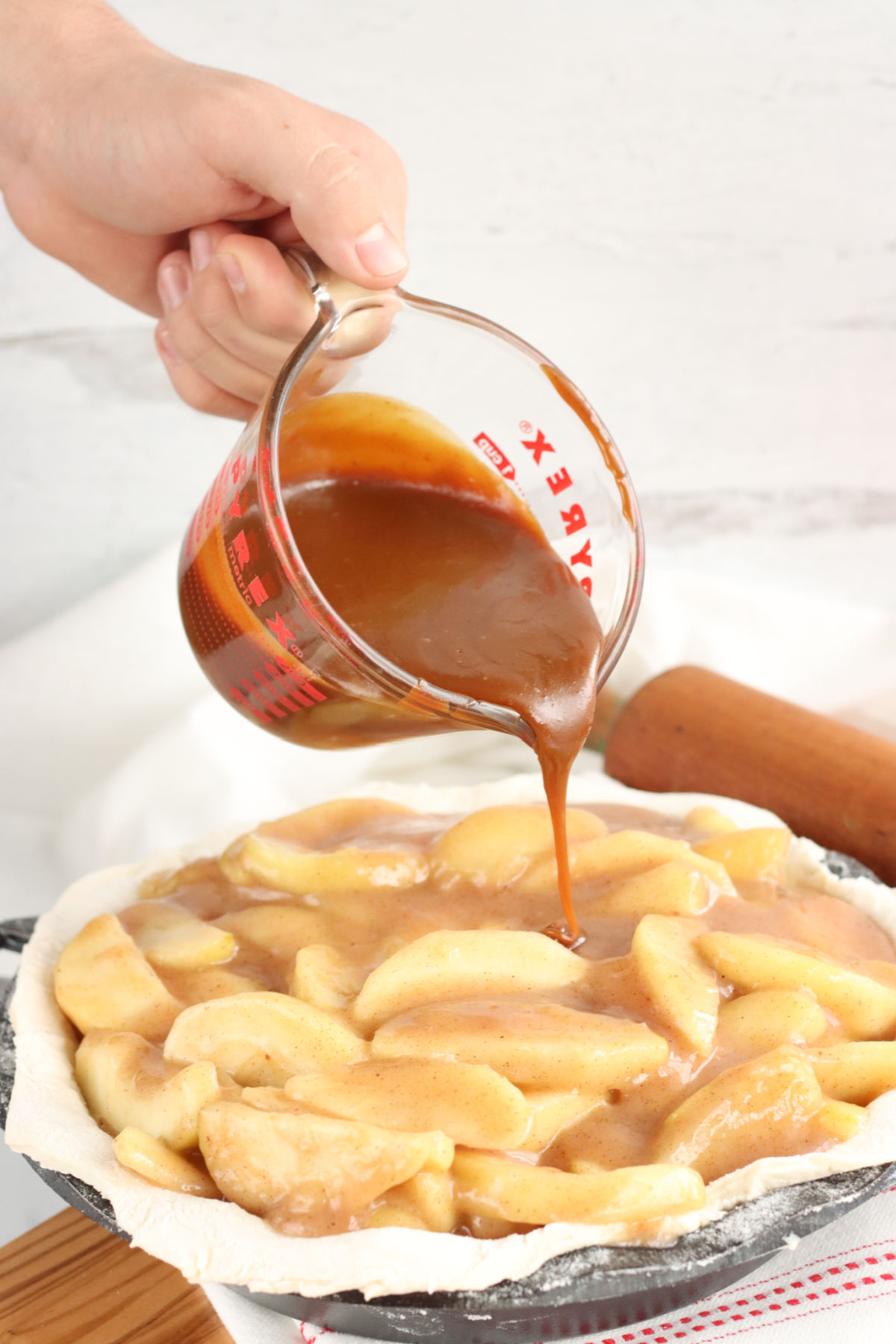 hand pouring caramel sauce over unbaked apple pie.