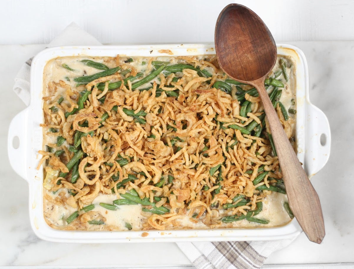 white ceramic baking dish with green bean casserole, wooden spoon on right edge of dish.