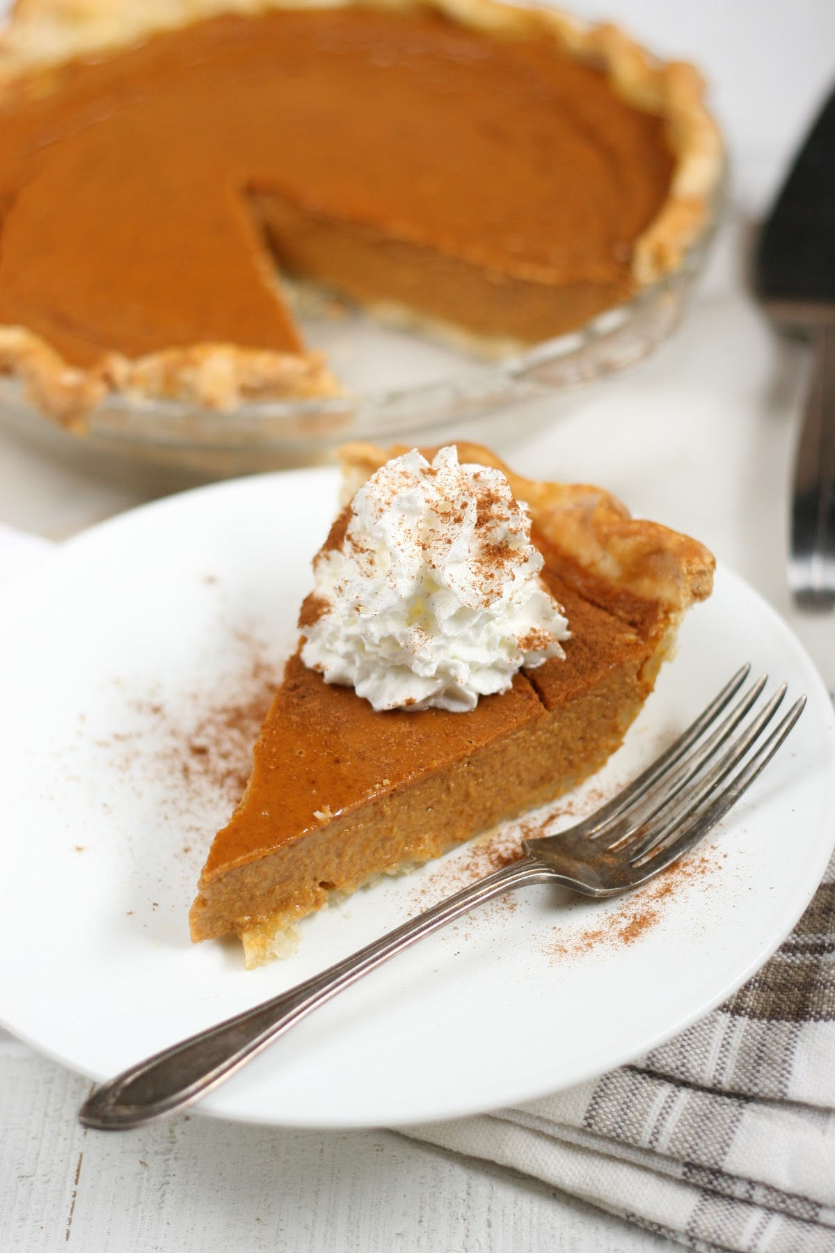 slice of pumpkin pie with whipped cream on small white plate with fork.