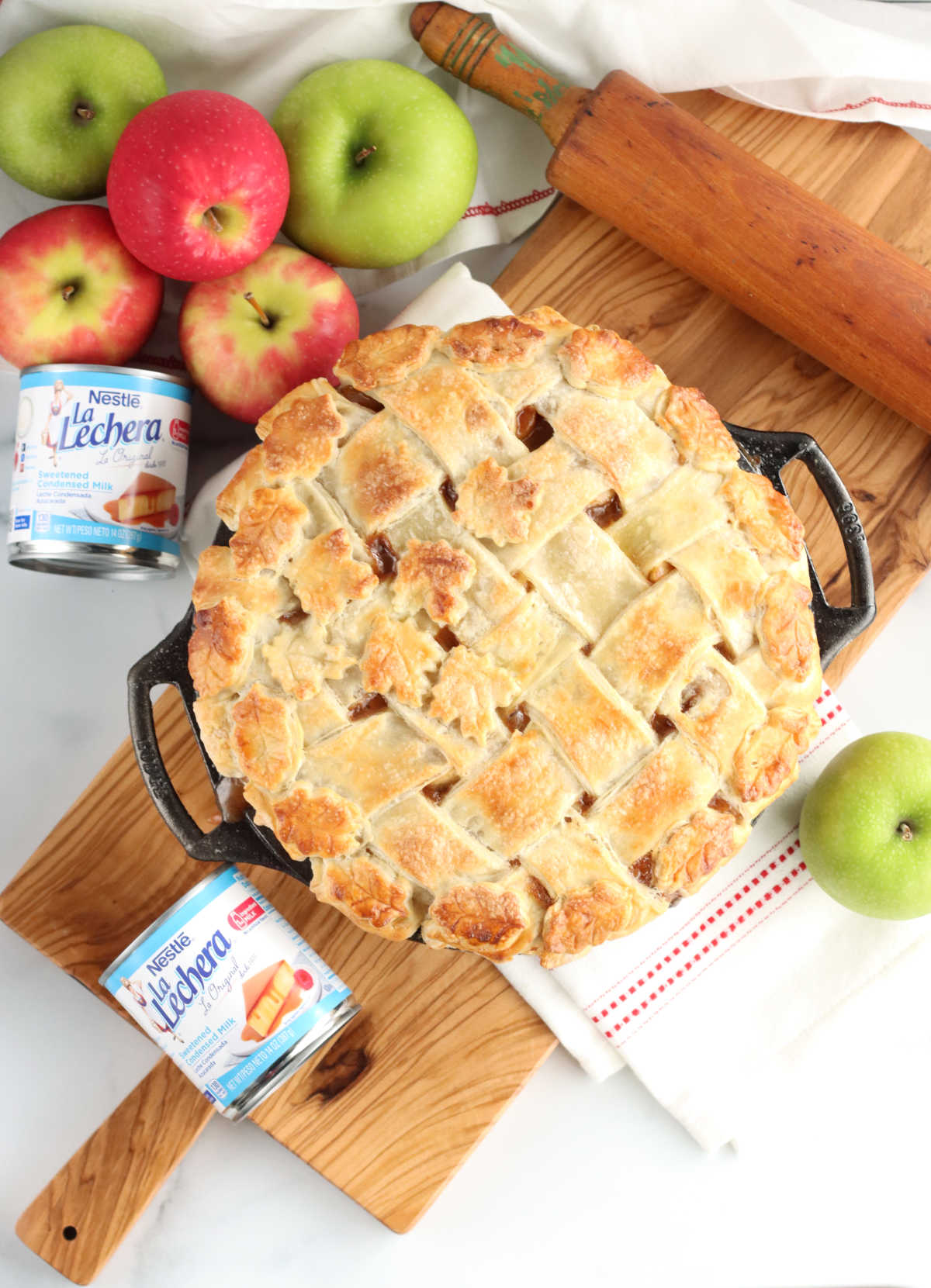 Apple pie with lattice crust on wooden cutting board, apples around it.