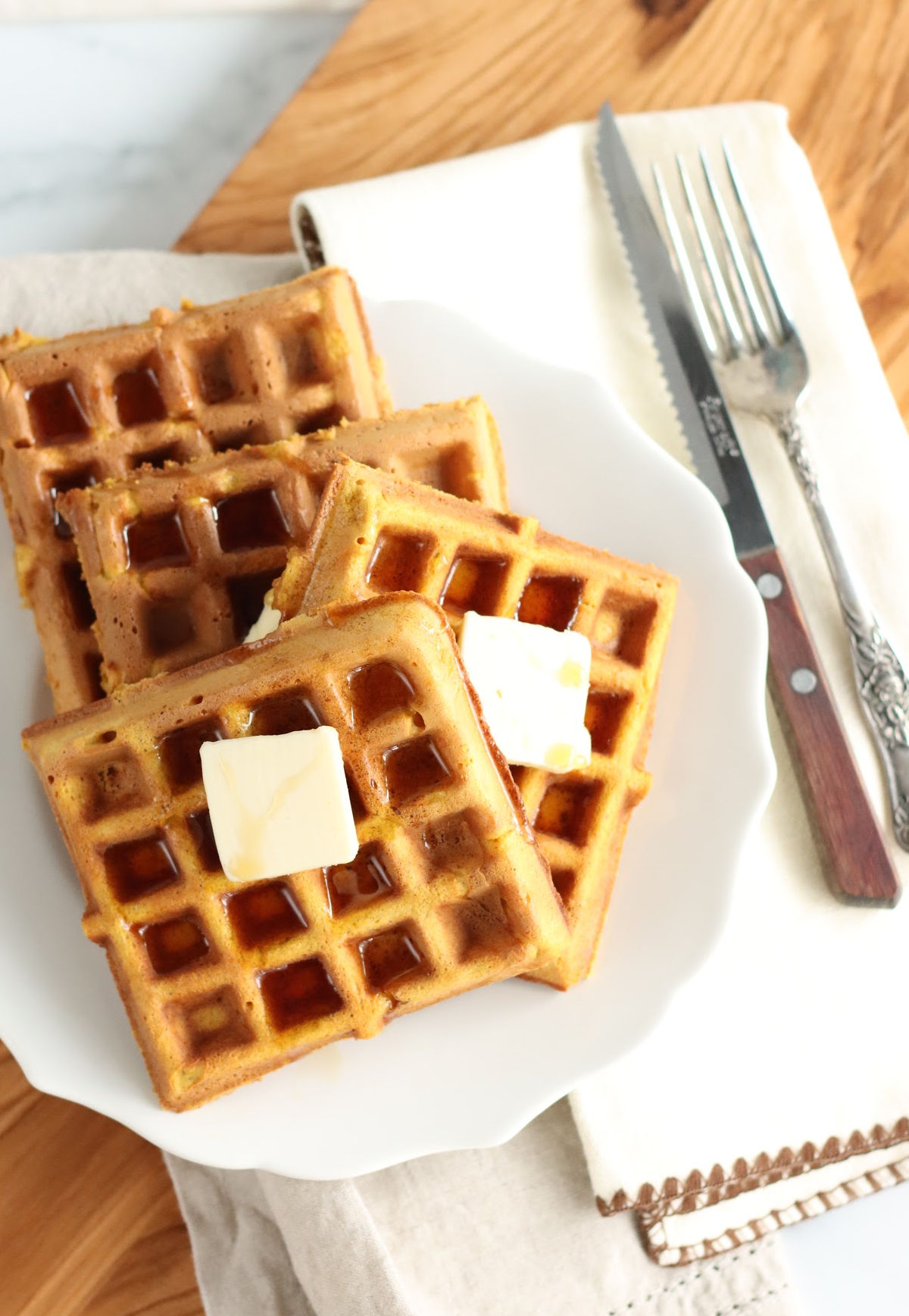 Square waffles stacked on each other, whipped cream, maple syrup, and sprinkled with cinnamon.