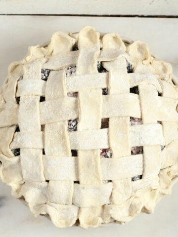 weaved lattice pie crust on berry pie before baking.