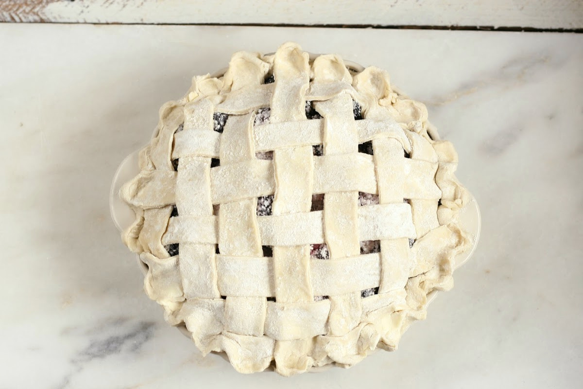 weaved lattice pie crust on berry pie before baking.