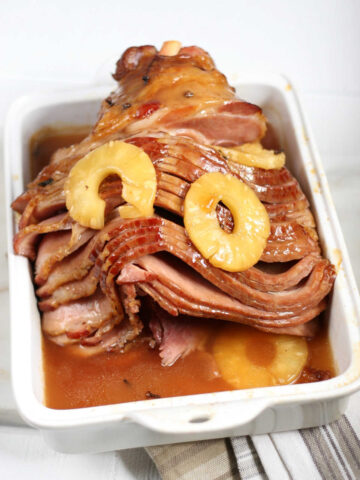 spiral sliced bone-in ham with pineapple slices in white rectangle baking dish.