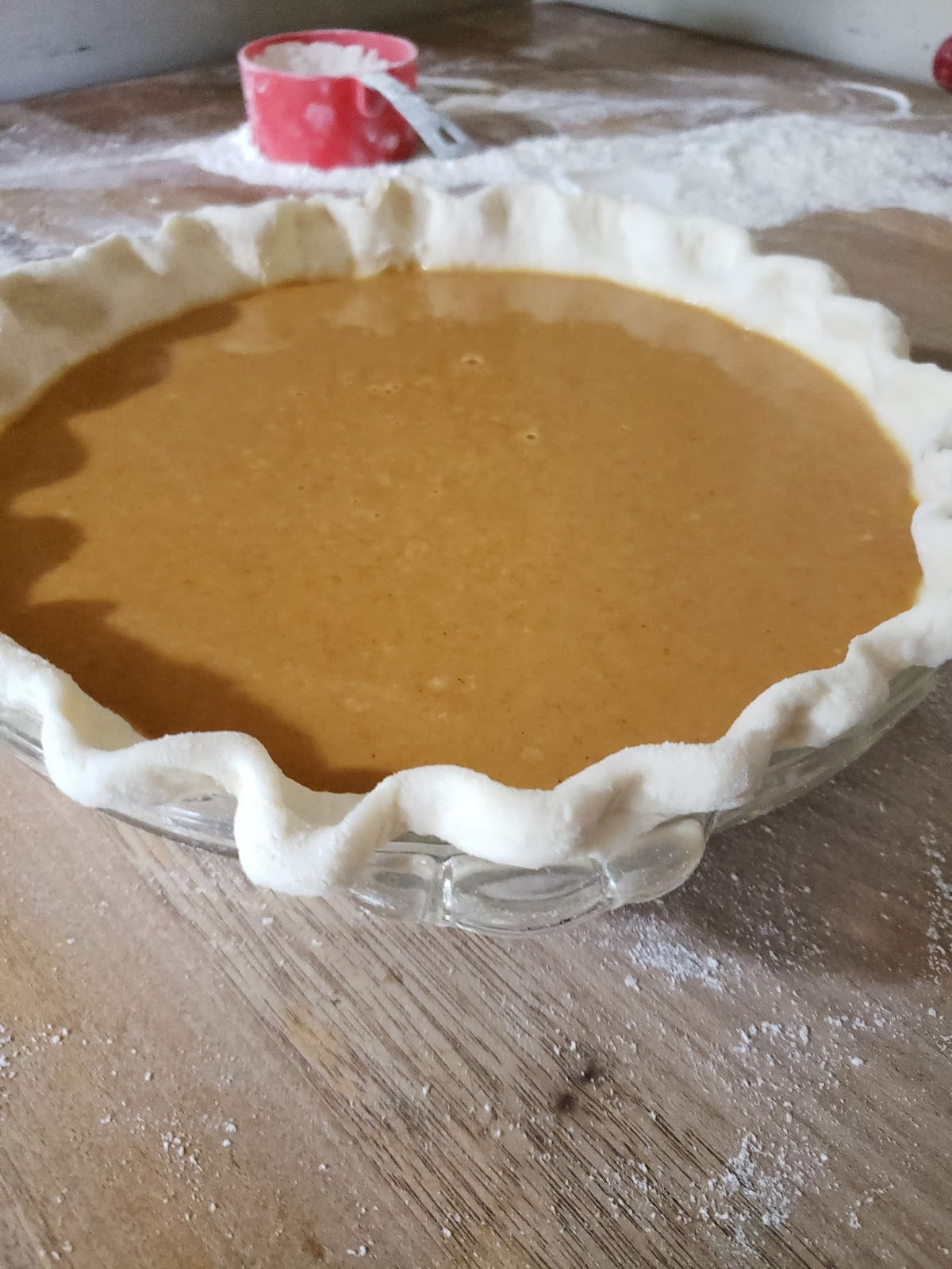 unbaked pumpkin pie on butcher block, red measuring cup with flour in background.