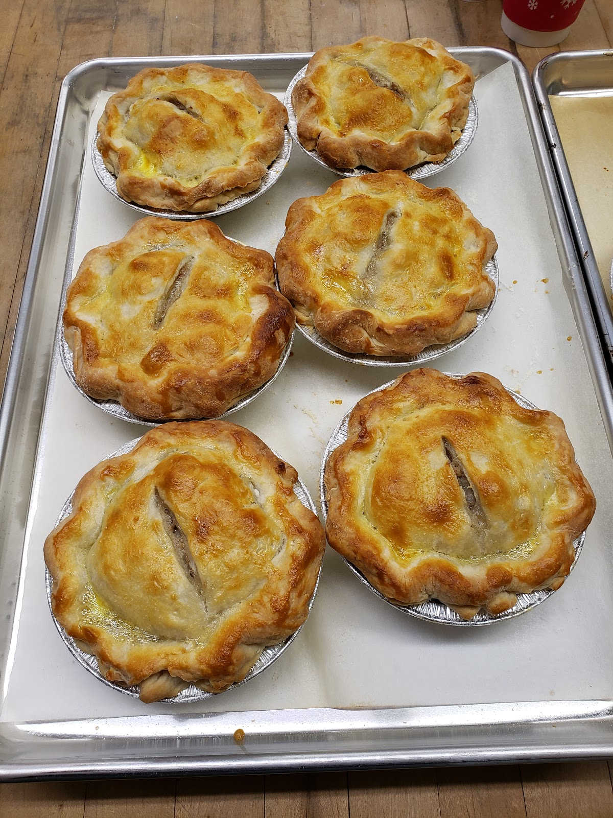 mini meat pies on sheet pan on butcher block.