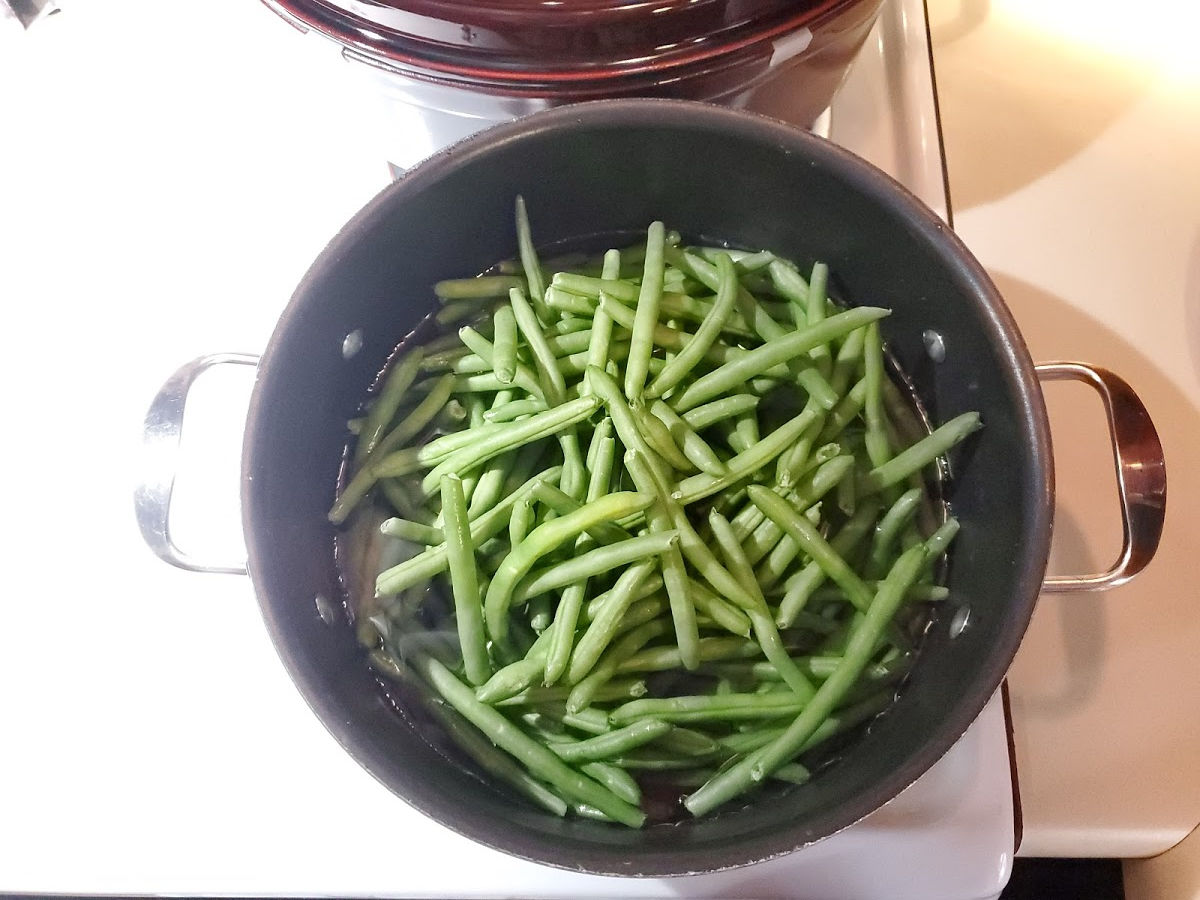 two handle pot on stove with blanched green beans.