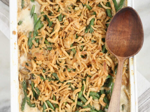 rectangle white baking dish with green bean casserole, wooden spoon on right edge of dish.