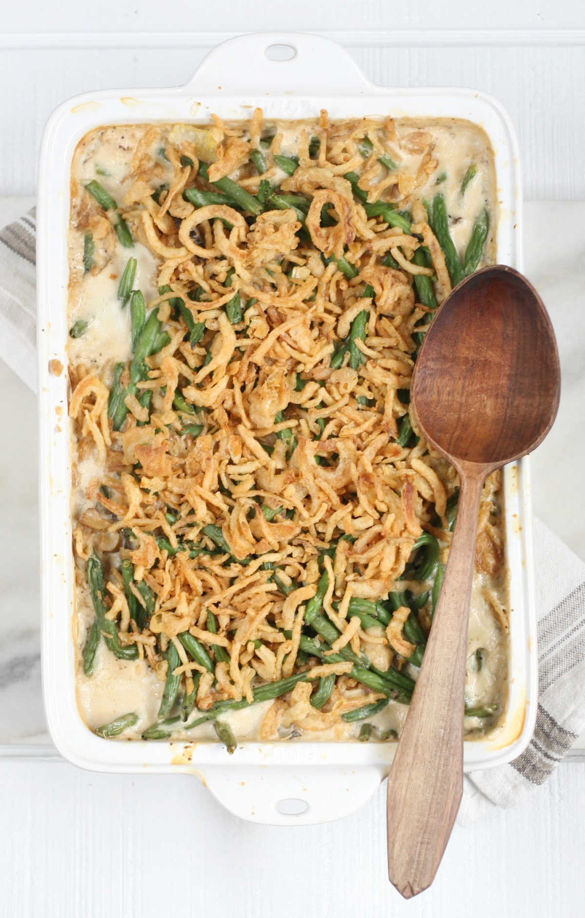 Rectangle white baking dish with green bean casserole, wooden spoon on edge of dish.