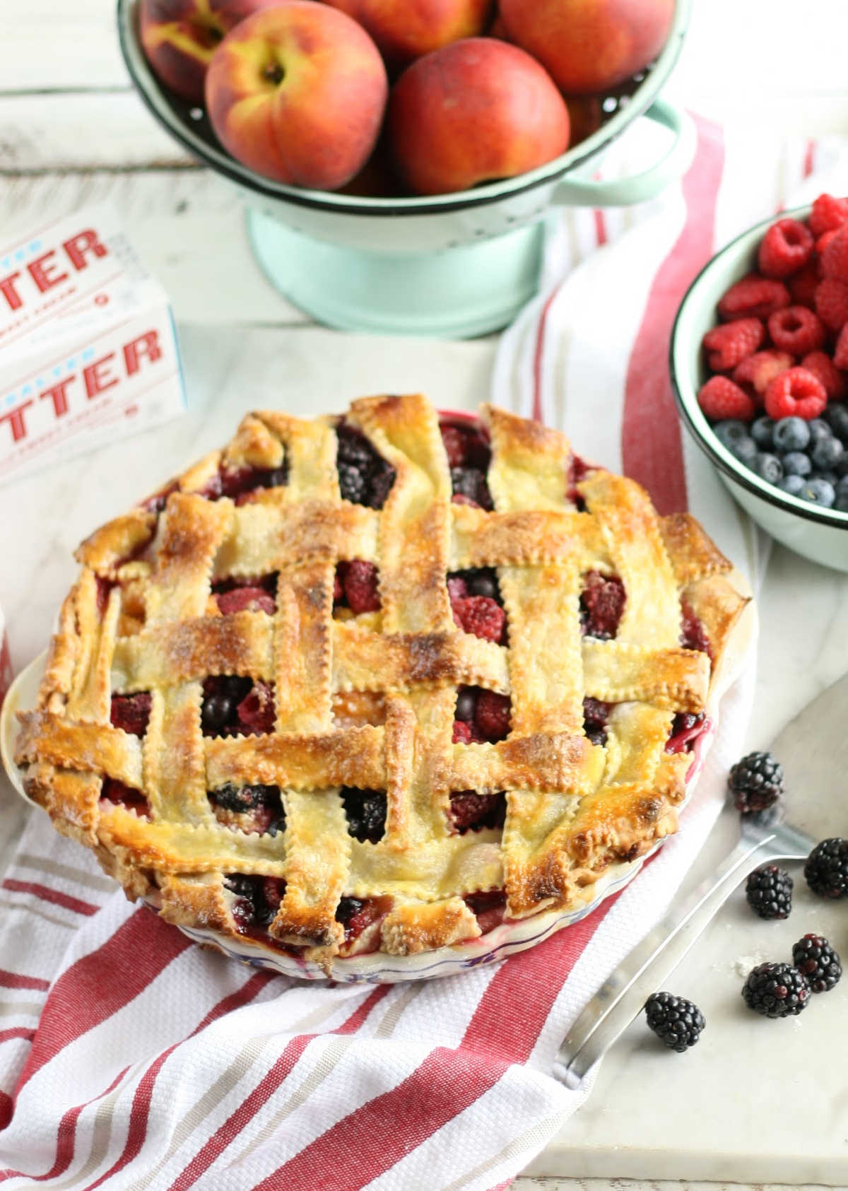 close up of triple berry pie with lattice crust on white and red striped kitchen cloth.