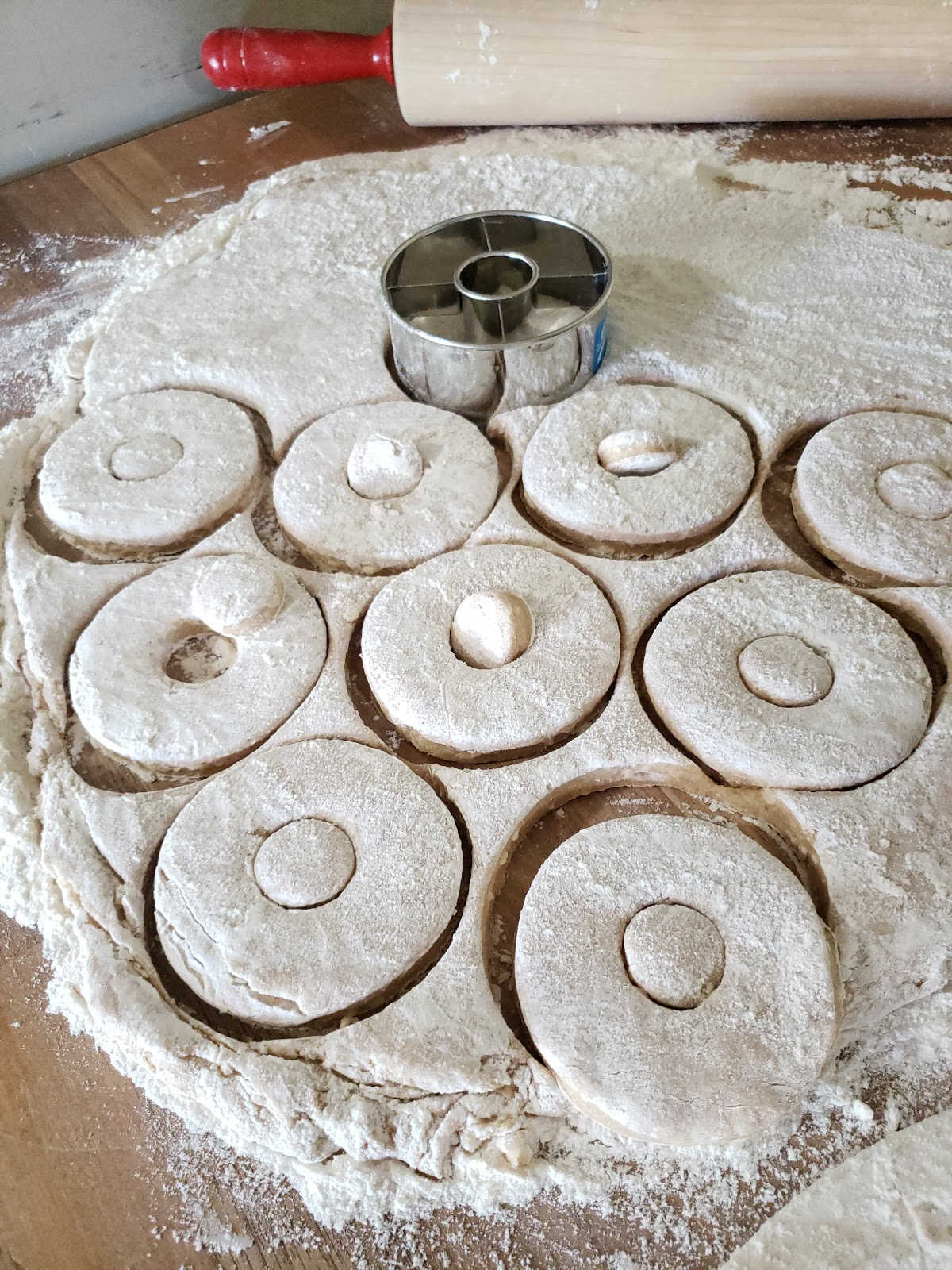 cutting donut dough with metal cutter on butcher block, red handled wooden rolling pin in background.