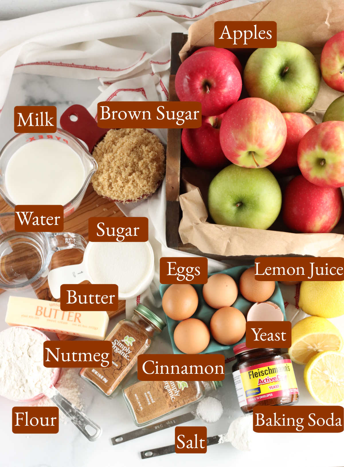 Overhead image of ingredients for apple fritters on wooden cutting board.