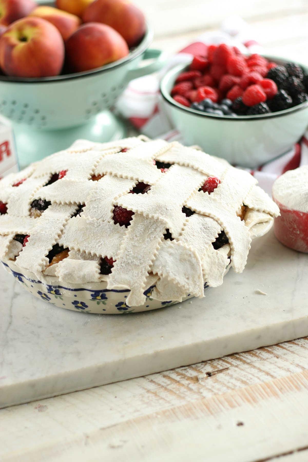 weaving lattice crust on berry pie in blue floral pie plate.