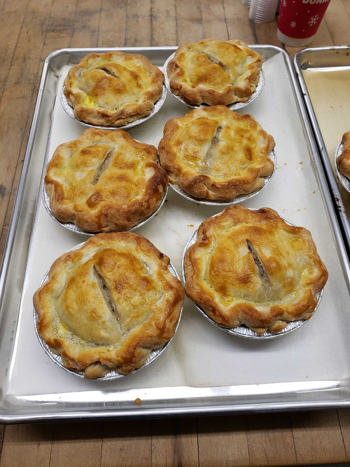 mini French meat pies on sheet pan on butcher block.