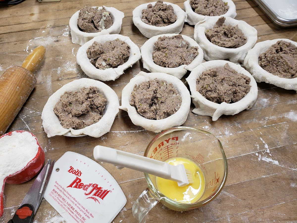 assembling mini  Meat pies on butcher block.
